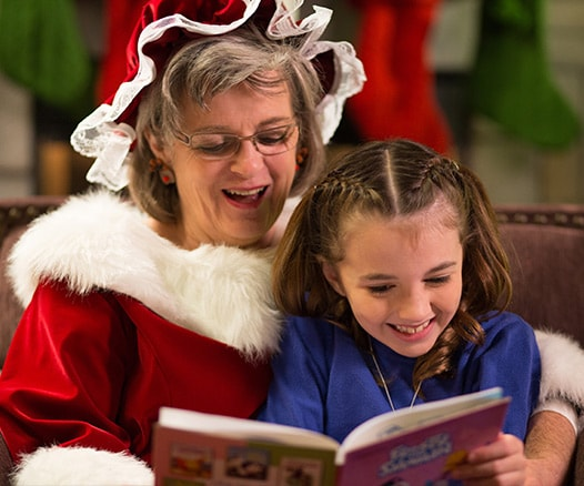 Young Girl and Mrs. Claus reading holiday classics during Lone Star Christmas at Gaylord Texan.