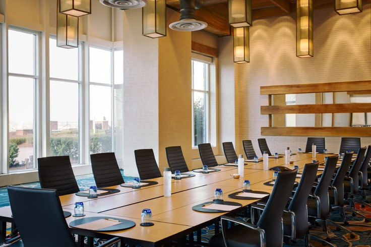 boardroom setting - long tables, chairs with notepads in front of each seat placement