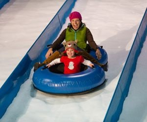 Family gliding down snow hill at Gaylord Opryland's A Country Christmas