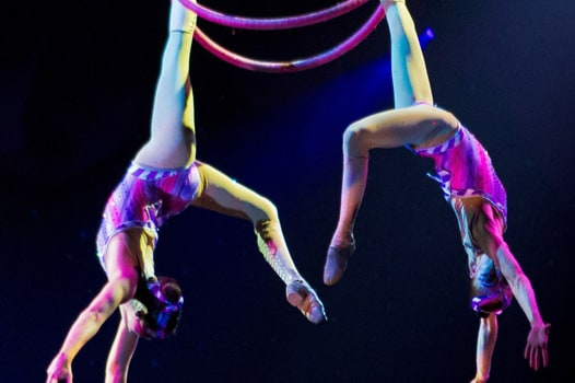 two aerialists mid-flight