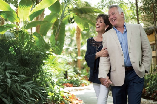 Couple walking in walkway amongt gardens in atrium at Gaylord Palms