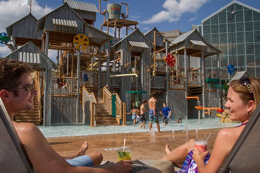Mom and Dad watching kids play and splash in water at Treehouse at Cypress Springs
