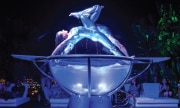 Two dancers perform in an over-sized glass bowl