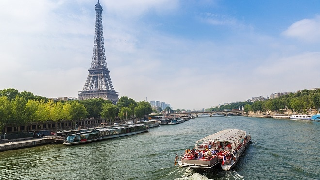 Eiffel tower overlooking Seine River with boat in foreground