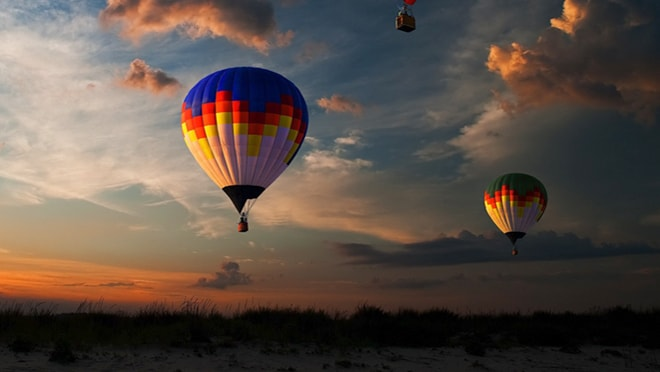 Three hot air balloons in sky at sunset