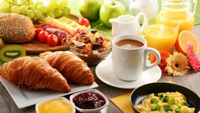 Frühstück mit Croissants, Kaffee, Rührei und Saft