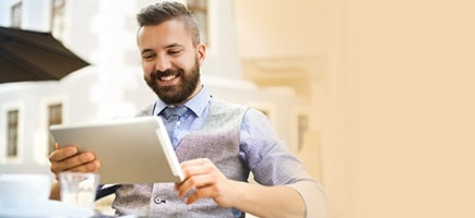 Young professional smiles while reading tablet