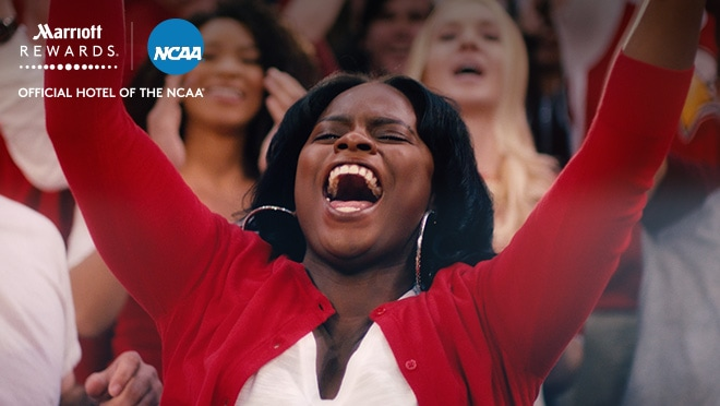 Female fan cheers. Marriott Rewards and NCAA logo. Official hotel of the NCAA.