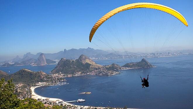 A man paraglides over the beaches of Rio de Janeiro