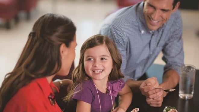 Lächelndes kleines Mädchen, das Eiscreme mit ihrer Familie isst