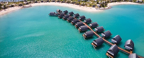 Bird's eye view of Caribbean beach and overwater bungalows