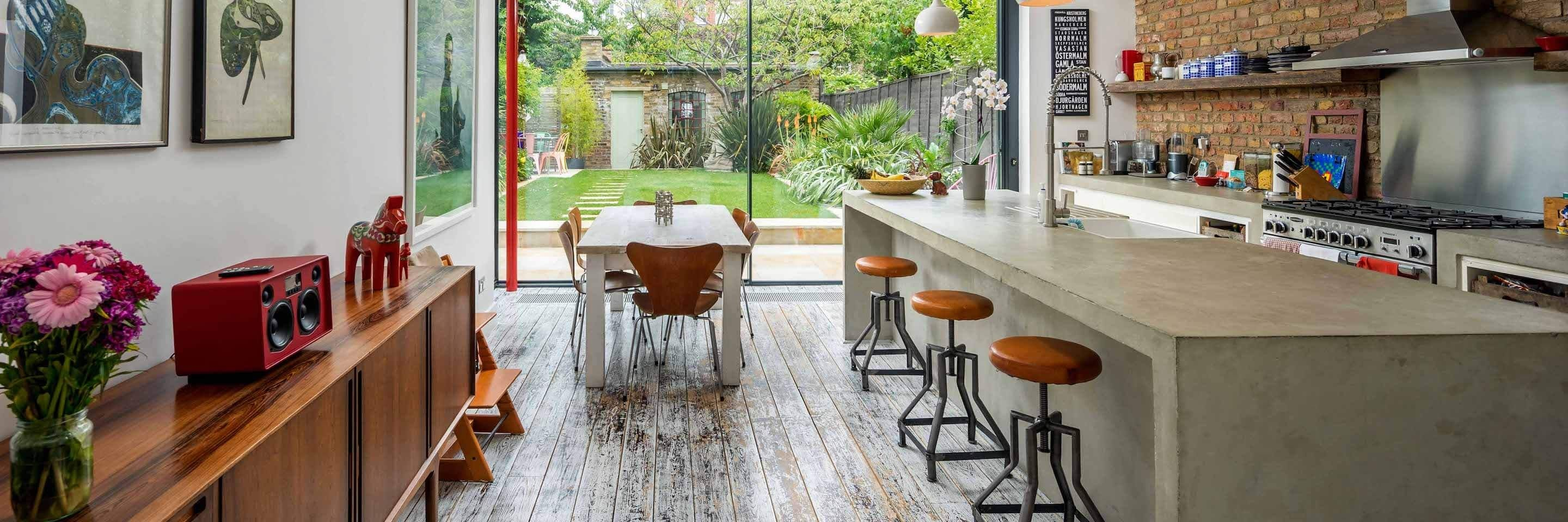 Kitchen interior featuring island bar and breakfast table, with view of outdoor garden.