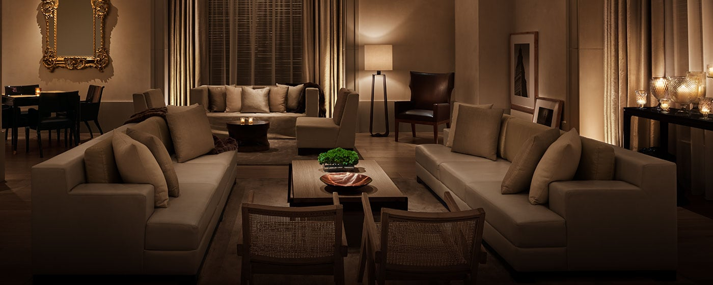 Luxurious candlelit sitting area with couches, chairs, and coffee table