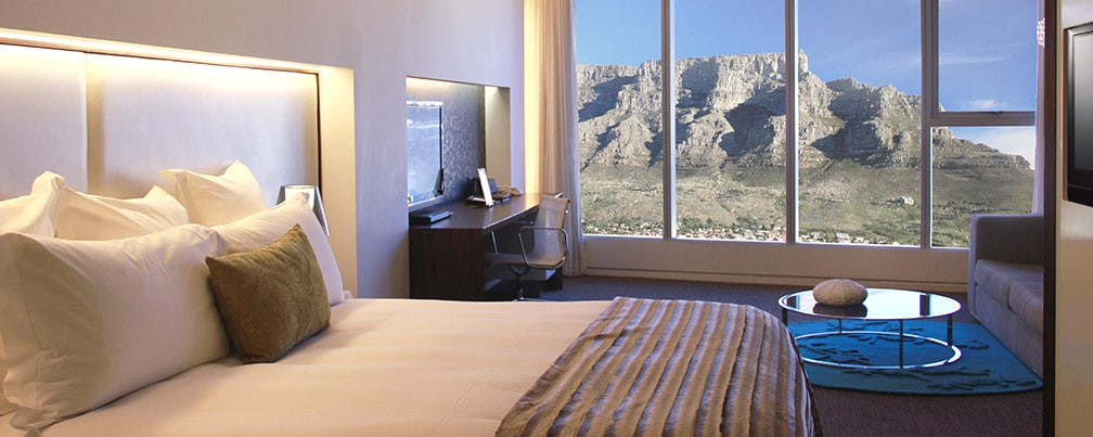 Room with king bed, flat-screen TV and a large window overlooking a mountain