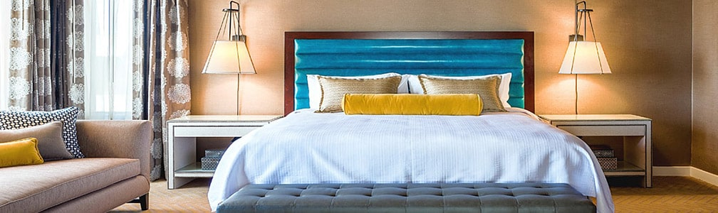 View of hotel room. Bed in center with blue headboard, yellow pillows, white duvet.
