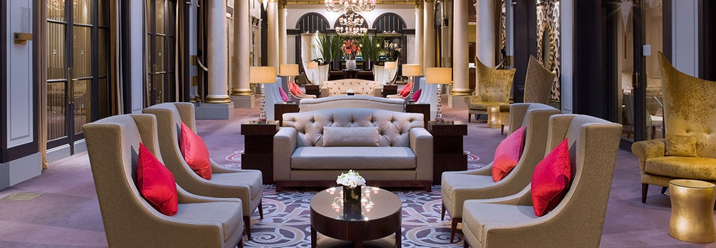 Luxurious hotel lobby with lounge seating, dramatic lighting and floral arrangements