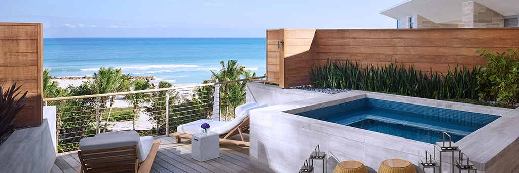 Balcony with hot tub and deck chairs overlooking the ocean at Miami Beach EDITION