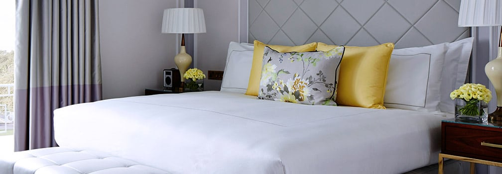 Guest room with king-sized bed, gold silk pillows and vases of fresh flowers.