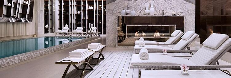 En el spa lujosos sillones reclinables junto a una moderna chimenea de piedra y vidrio