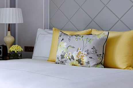 Guest room with king-sized bed, gold silk pillows and vases of fresh flowers