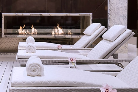 Luxurious spa recliners beside modern stone and glass fireplace
