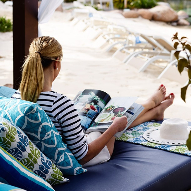 A woman sits on a lounge chair reading a magazine
