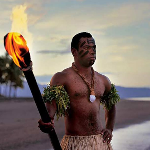 A fijian man holds a torch on the beach