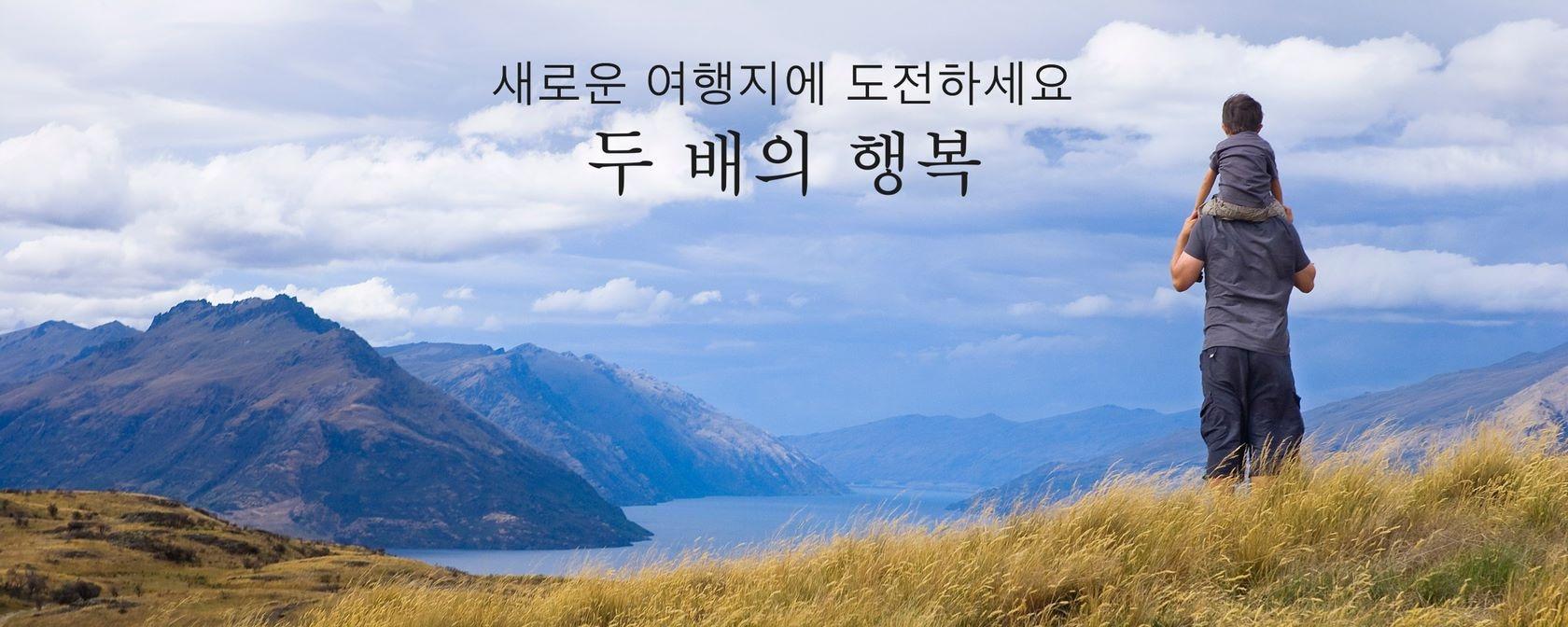 호수와 산이 내려다보이는 푸르른 산 정상에 서 있는 어른과 아이