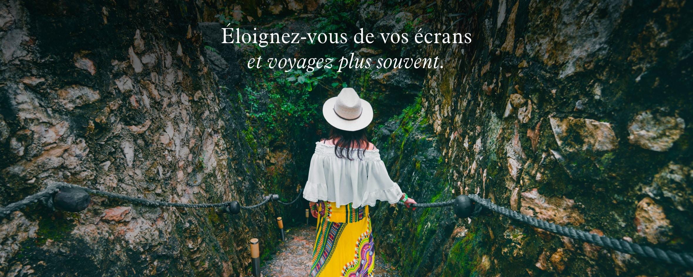 Femme vêtue d'une robe aux couleurs vives en train de descendre des escaliers en pierre.