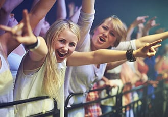 Young people cheering at concert