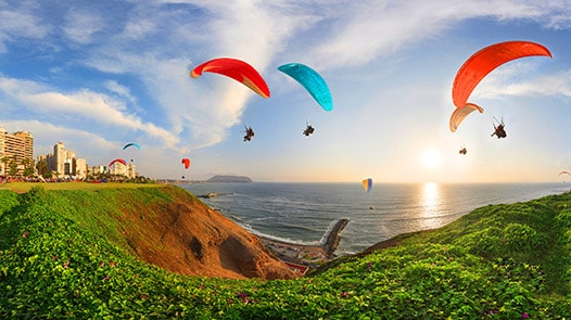 Parachutists floating above cliff and sea