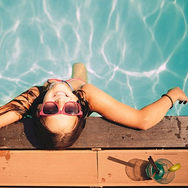Overhead view of woman wearing pink sunglasses while standing in swimming pool.