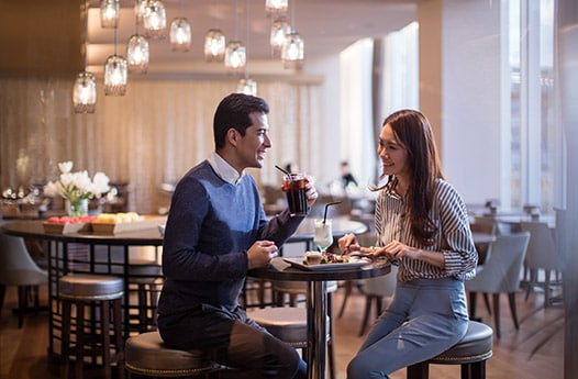Man and woman eating and drinking in hotel restaurant