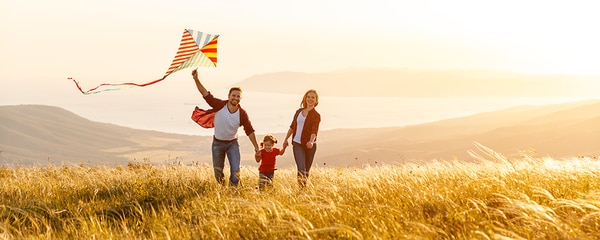 Happy family at a coast launching a kite at sunset