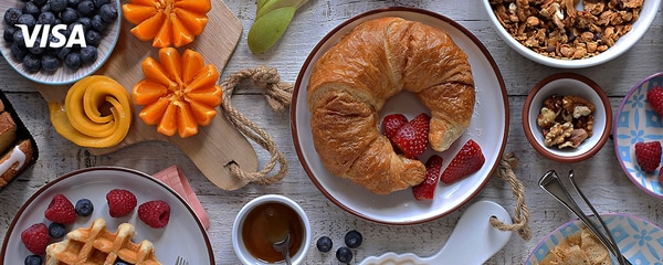 Breakfast with granola, croissant, fresh waffles, fruits and berries