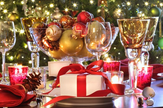 Holiday table setting with gift and wine glasses