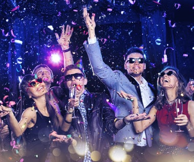 People dressed in party clothes celebrating on New Year's Eve