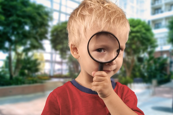 blonde boy looking through magnifying glass