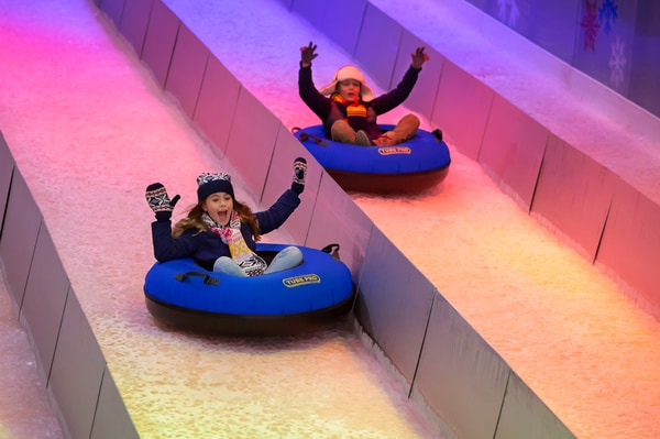 children going downhill on an inflatable tube on a snow slide