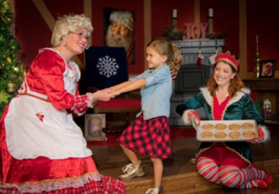 mrs claus greeting a child and an elf woman with cookies