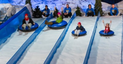 people going down a snowy incline on inflatable tubes