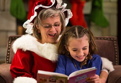 Mrs. Claus reading a book to a child