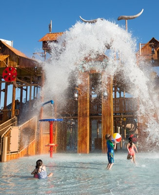 Children playing in shallow pool with spraying water at Paradise Springs water park