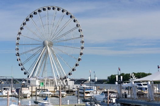 Captal ferris wheel and boats in harbor