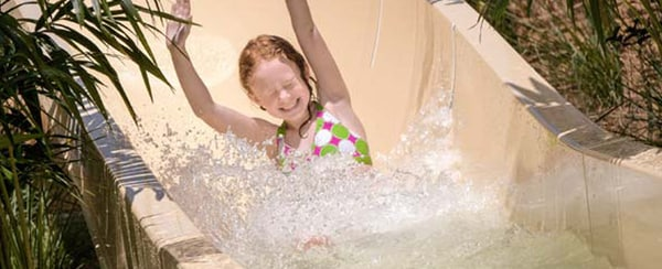 Girl going down the slide with hands up at Cypress Springs at Gaylord Palms