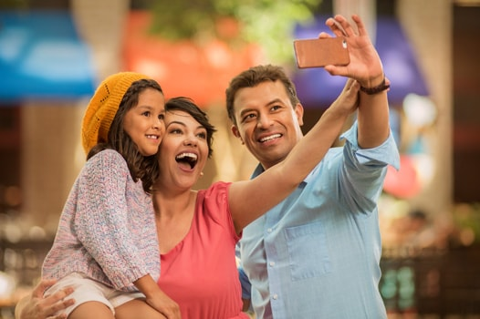 Family of three taking a selfie and smiling