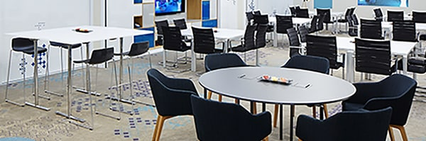 Meeting space with round, rectangular and high-top collaboration tables in a bright, open setting.
