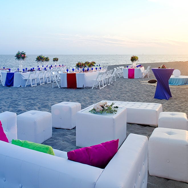 Dining tables and seating area on the beach set for a party