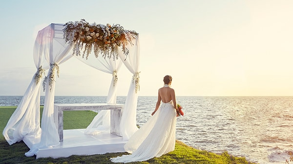 Bride standing by oceanside altar