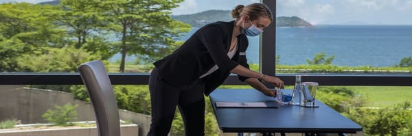 Woman with facemask preparing meeting set-up in meeting room with sea views.